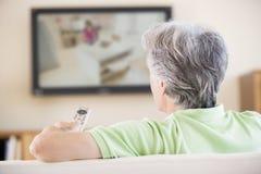 Het letten op van de mens televisie die afstandsbediening met behulp van Stock Fotografie