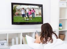 Het Letten op van de vrouw Televisie Royalty-vrije Stock Afbeeldingen