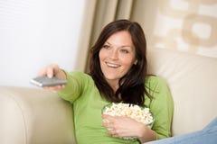 Het letten op van de vrouw televisie met popcorn royalty-vrije stock afbeelding