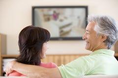 Het letten op van het paar televisie het glimlachen stock afbeelding