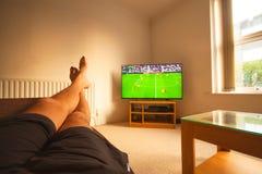 Het letten op voetbal op TV stock fotografie