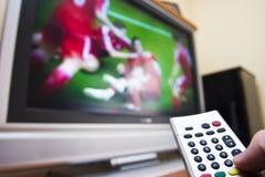 Het letten op voetbal op TV stock afbeelding