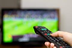 Het letten op voetbalspel op TV Stock Afbeeldingen