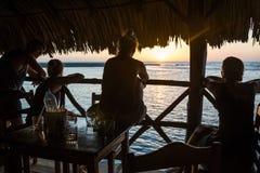 Het letten van de op zonsondergang in een bar bij de oceaan Royalty-vrije Stock Foto's