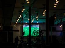 Het letten van een op voetbalspel op het scherm binnen een koffie/restaurant bij nacht stock foto