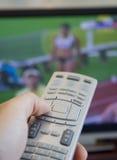 Het letten van op olympische spelen op TV stock foto's