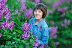 Het leuke aanbiddelijke mooie meisje van de damevrouw met donkerbruin haar op een weide van lilac purpere struik Mensen in jeanss royalty-vrije stock foto
