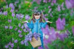 Het leuke aanbiddelijke mooie meisje van de damevrouw met donkerbruin haar op een weide van lilac purpere struik Mensen in jeanss stock afbeelding