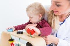 Het leuke actieve babyjongen spelen met speelgoed tijdens fysiek onderzoek royalty-vrije stock afbeelding