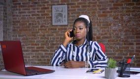 Het leuke Afrikaanse meisje spreken over telefoon en glimlachen met ontspannen bekijken binnen op het haar werk stock videobeelden