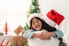 Het leuke Aziatische dochtermeisje geeft haar een moederomhelzing stock afbeeldingen