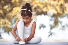 Het leuke Aziatische kindmeisje binden op voeten pointe schoenen Royalty-vrije Stock Afbeelding