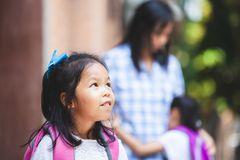 Het leuke Aziatische kindmeisje die haar zuster wachten gaat samen naar school na omhelzing hun moeder royalty-vrije stock foto's