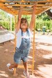 Het leuke Aziatische kindmeisje hangt de bar door haar hand om in de speelplaats uit te oefenen royalty-vrije stock afbeeldingen
