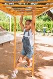Het leuke Aziatische kindmeisje hangt de bar door haar hand om in de speelplaats uit te oefenen stock foto