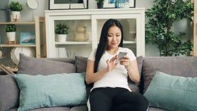Het leuke Aziatische meisje gebruikt smartphone wat betreft het scherm en glimlacht het ontspannen bij bank thuis alleen van mode stock videobeelden