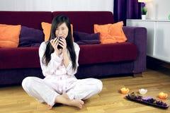 Het leuke Aziatische meisje ontspant door een aftreksel te drinken Stock Afbeeldingen