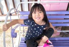 Het leuke Aziatische meisje zit bij schommeling en het glimlachen Royalty-vrije Stock Afbeeldingen