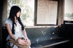 Het leuke Aziatische Thaise meisje in uitstekende kleren wacht alleen Royalty-vrije Stock Afbeelding