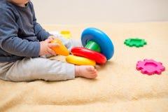 Het leuke baby spelen met kleurrijke stuk speelgoed piramide in lichte slaapkamer Speelgoed voor kleine jonge geitjes Kind met on royalty-vrije stock fotografie