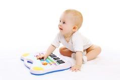 Het leuke baby spelen met stuk speelgoed piano op een wit Stock Foto