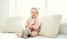 Het leuke baby spelen met teddy stuk speelgoed huis in witte ruimte dichtbij wind Royalty-vrije Stock Foto's