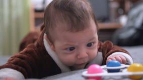 Het leuke babyjongen oude liggen van drie maanden op zijn maag stock footage