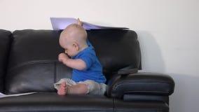 Het leuke babyjongen spelen met documentendocumenten op bank stock videobeelden