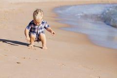 Het leuke babyjongen spelen met zand op het strand De ruimte van het exemplaar Royalty-vrije Stock Afbeeldingen