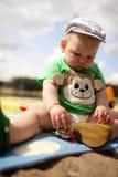 Het leuke babyjongen spelen in zand Stock Afbeelding