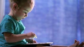 Het leuke babymeisje gebruikt een Tabletpc, aanrakingenvinger