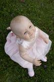 Het leuke babymeisje in gras kijkt omhoog royalty-vrije stock fotografie