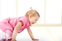 Het leuke babymeisje kruipen stock foto