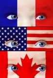 Het leuke babymeisje met de vlaggen van Frankrijk, van de V.S. en van Canada schildert op haar gezicht Stock Afbeeldingen