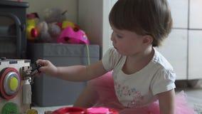Het leuke babymeisje spelen met stuk speelgoed thuis stock video