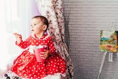 Het leuke babymeisje spelen naast het venster royalty-vrije stock fotografie
