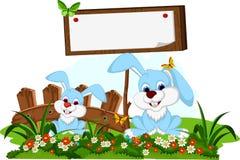 Het leuke beeldverhaal van het paarkonijn met lege raad in bloemtuin Stock Afbeelding