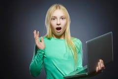 Het leuke benieuwd zijn of beklemtoond meisje die laptop geïsoleerde grijze achtergrond gebruiken Royalty-vrije Stock Foto's
