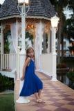 Het leuke blonde Kaukasische meisje in blauwe kleding leunt tegen een pijler De avondscène met gazebo is op de achtergrond stock fotografie