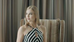 Het leuke blonde kijkt weg zittend in een leunstoel in hotelruimte stock video
