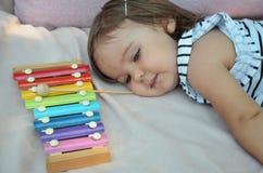 Het leuke blonde kind spelen met xylofoon thuis Creativiteit en onderwijsconcept royalty-vrije stock afbeelding
