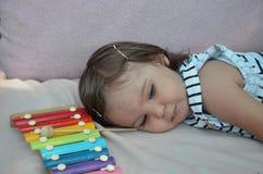 Het leuke blonde kind spelen met xylofoon thuis Creativiteit en onderwijsconcept royalty-vrije stock fotografie