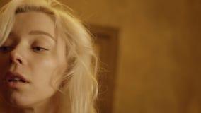Het leuke blonde krullende haired meisje kijkt rond op onscherpe lichtbruine achtergrond stock video