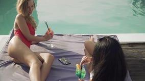 Het leuke blonde met slanke benen heeft vrolijke dialoog met mooi brunette op de zitkamer dichtbij openlucht zwembad Twee stock video