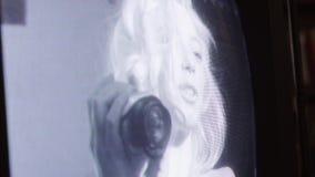 Het leuke blondemeisje die kleine camera houden wordt in hand getoond op retro TV-scherm stock videobeelden