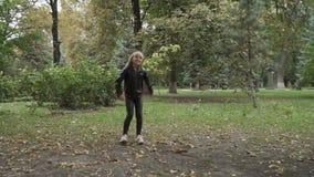 Het leuke blondemeisje springt in het park en verzendt luchtkus naar camera stock videobeelden