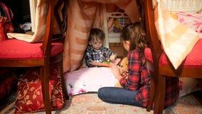 Het leuke boek van de de jongenslezing van de 1 éénjarigepeuter met oudere zuster in tent bij slaapkamer stock afbeeldingen