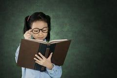 Het leuke boek van de meisjeslezing in klaslokaal royalty-vrije stock afbeelding