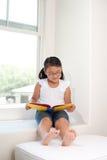 Het leuke boek van de meisjeslezing op venster Royalty-vrije Stock Afbeelding