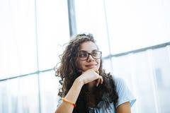Het leuke Braziliaanse meisje die met krullend haar aan een gesprek luisteren en heeft een idee royalty-vrije stock afbeelding